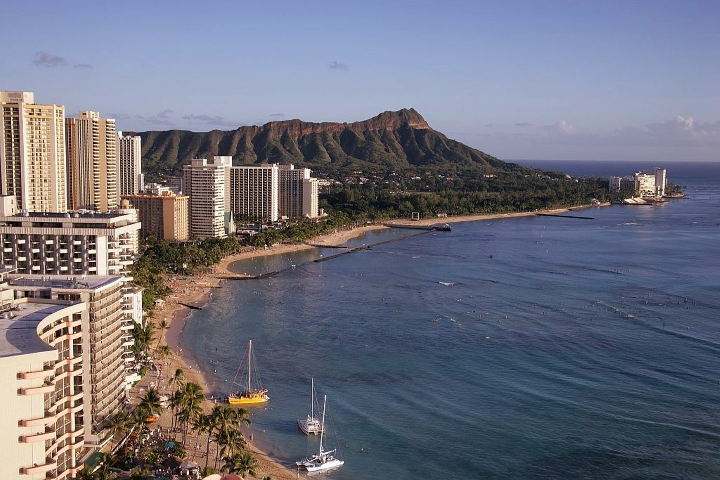 Aerial shot of the coastline of Waikiki with the ocean, Diamond Head, and the hotels.