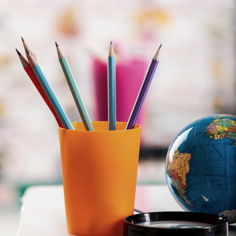 Cup of color pencils with a small globe next to it.
