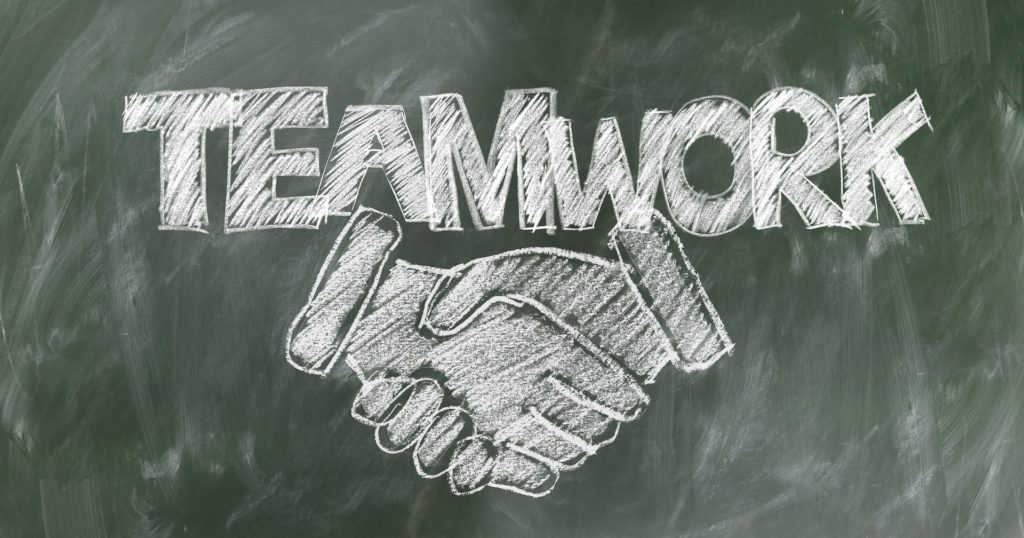"""On a chalkboard, two hands shaking with """"teamwork"""" written above the hands."""