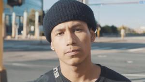 Young man wearing dark beanie cap looking at camera.
