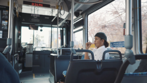 """Young man wearing dark beanie cap sitting on city bus. Sign on the window behind him says 'Wheelchair seating area."""""""