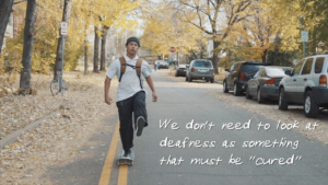 """Young man in dark beanie, with his left leg raised, skateboarding down a street on a fall day. Fallen leaves line the street.. Text on image says """"we don't need to look at deafness as something that must be 'cured.'"""