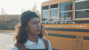 """Young man in dark beanie, looking pensively, standing beside a school bus. Text on image says """"I always had a really hard time communicating with others."""""""
