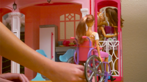 Girl's right hand moves a doll in a wheelchair into playhouse. Other dolls standing in the house are looking away from her and embracing each other.