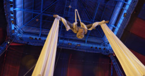 Low angle view of woman hanging upside down from silk strap.