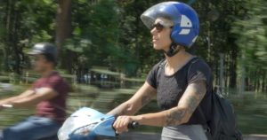 Woman on motorcycle, wearing helmet and backpack.
