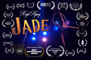"""Movie Poster for 'High Flying Jade."""" It features low angle shot of woman on a trapeze holding a hoop. It also lists many awards won by the film."""