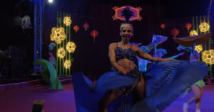 Dancing woman in flowing costume in front of variously colored lights, some shaped like flowers.