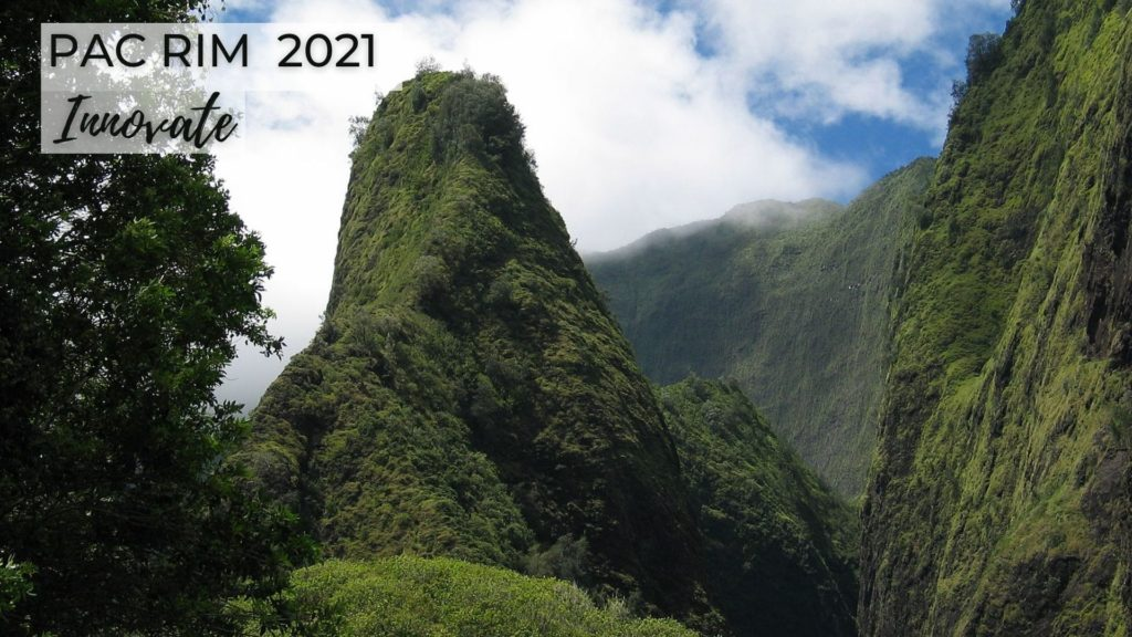 "Photo of ʻIao Needle on the island of Maui. There is a pointed mountain peak in the middle and a big tree to the left and a green mountain to the right. There are white clouds in the blue sky above. In the left upper corner it says ""Pac Rim 2021 and Innovate."""